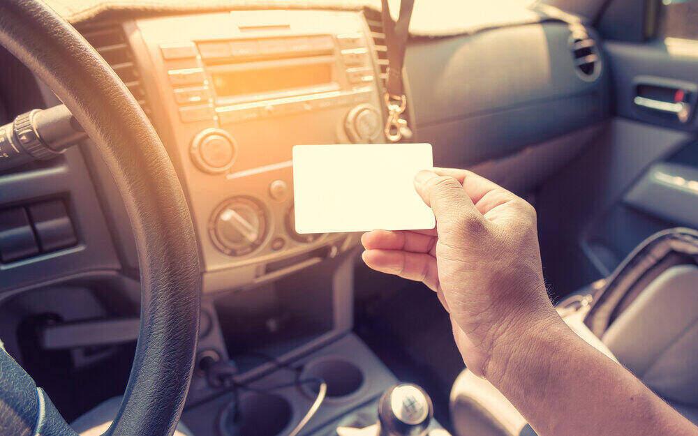Araç Kiralamak için Ehliyet Şart mı? Otomobil iç mekanda kartvizit tutan el